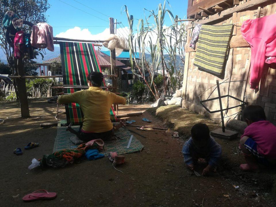 織物をするお母さんの周りで子供たちが遊んでいた
